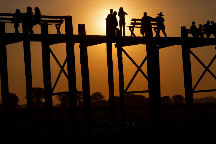 Low angle view of silhouette people on u bein bridge during sunset against sky