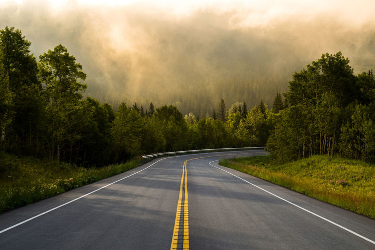Sunrise at Waterton Lakes National Park, Canada. Asphalt Beauty In Nature Day Dividing Line Forest Nature No People Outdoors Road Road Marking Scenics Sky Sunrise The Way Forward Tranquility Transportation Tree