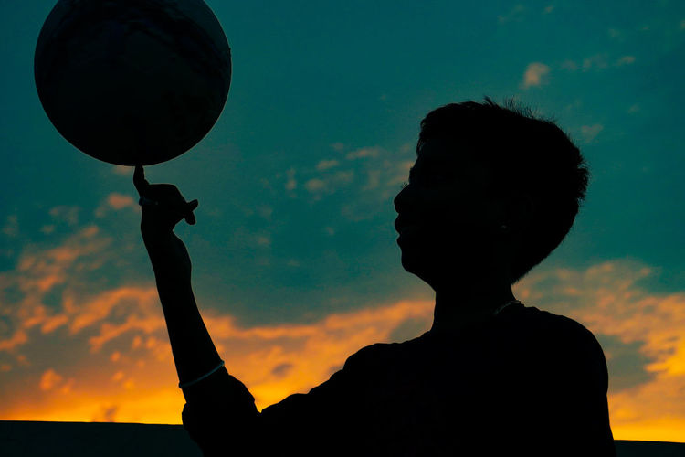 Low angle view of silhouette man holding orange sky during sunset