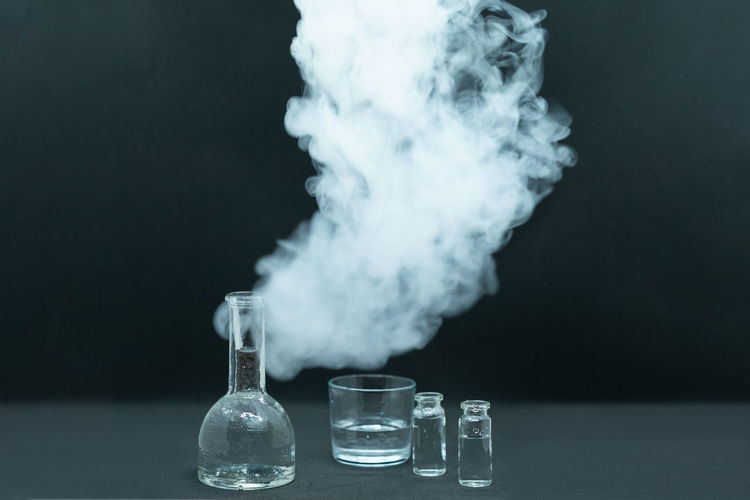 Close-up of smoke emitting from glass over black background