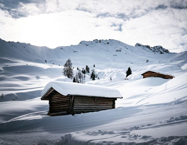 Scenic view of shack on snow covered mountains against sky