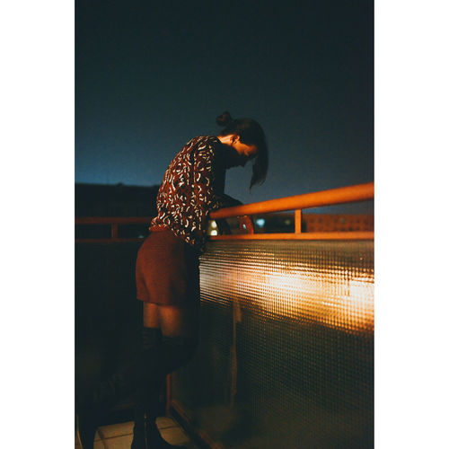 Side View Of Woman Standing By Railing Against Sky At Night