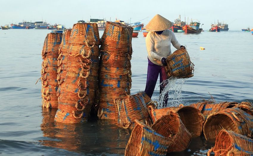 Woman washing old whicker baskets in sea