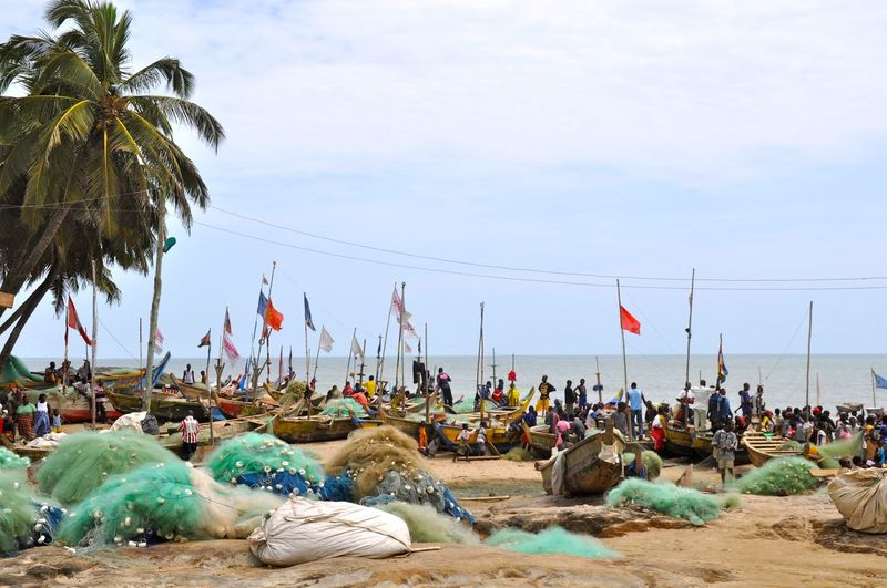 People By Boats And Fishing Nets At Beach Against Sky