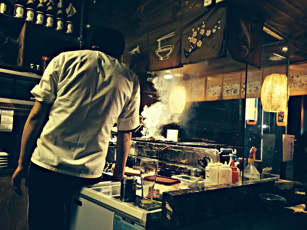 Rear View Of Man Cooking In Kitchen At Restaurant