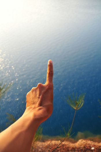Close-Up Of Person Gesturing Against Lake