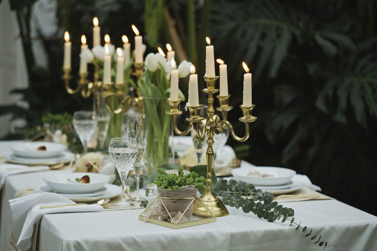 View of dining table with candles against plants