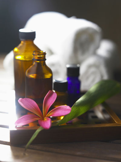 Bottles of aromatherapy oil and flower with rolled up towels in the background Frangipani Aromatherapy Beauty In Nature Beauty Spa Bottle Close-up Day Essential Oils Flower Flower Head Freshness Health Spa Indoors  Leaf Massage Oil Nature No People Petal Roll Towel Selective Focus Table Tower Water