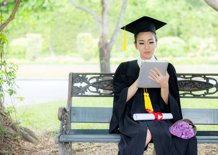 One Person Front View Young Adult Holding Real People Young Women Wireless Technology Focus On Foreground Achievement Graduation Gown Day Graduation Technology Black Color Mortarboard Standing Connection Women Outdoors