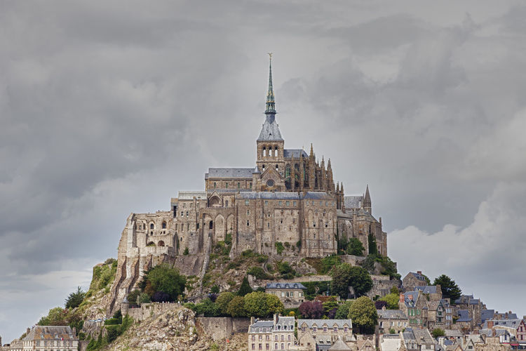 Low angle view of mont saint michel abbey against cloudy sky
