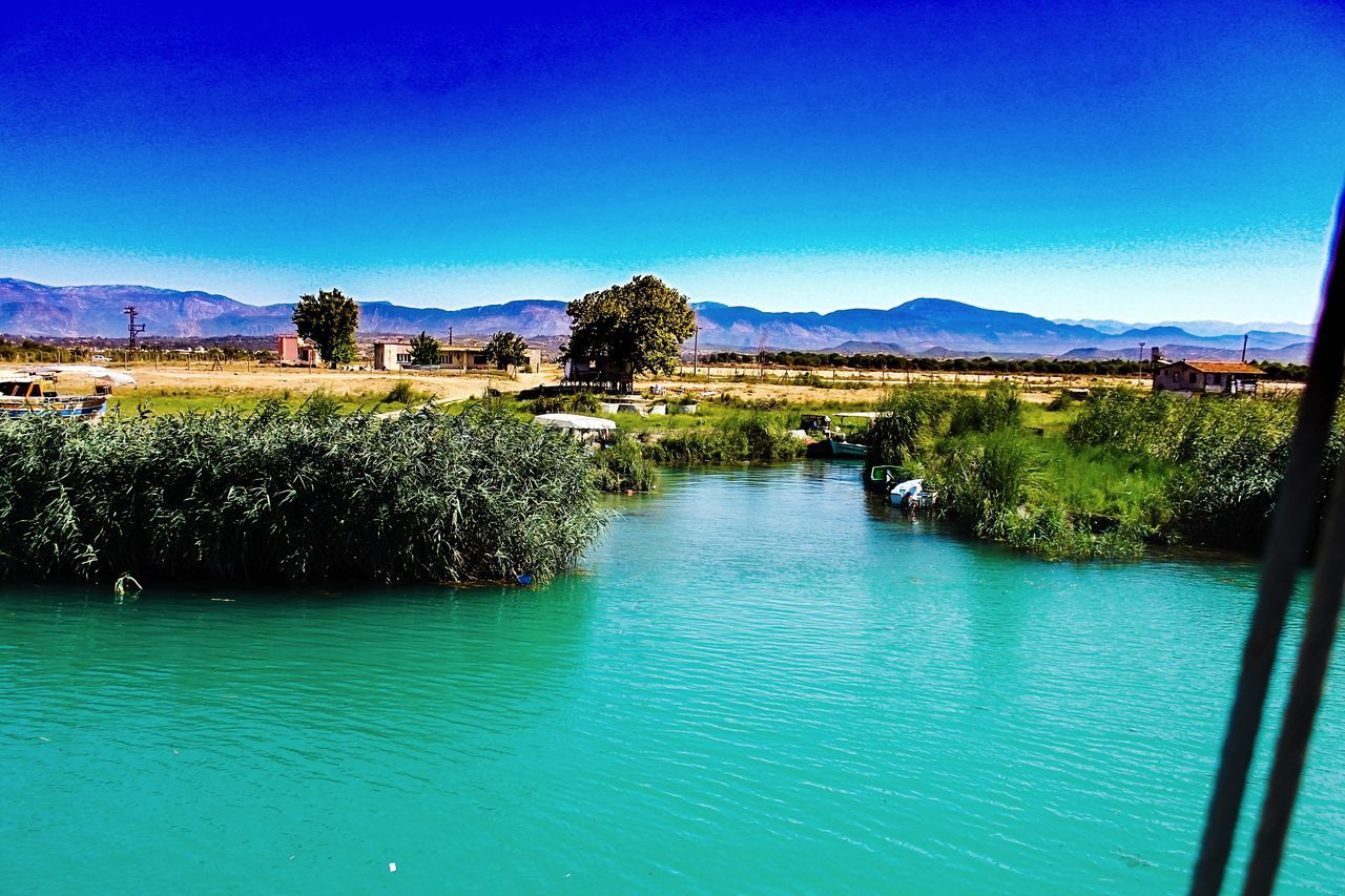 water, blue, tranquil scene, scenics, clear sky, mountain, outdoors, nature, lake, beauty in nature, tranquility, waterfront, no people, day, tree, landscape, architecture, sky, building exterior