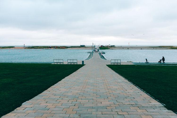 Footpath by sea against sky