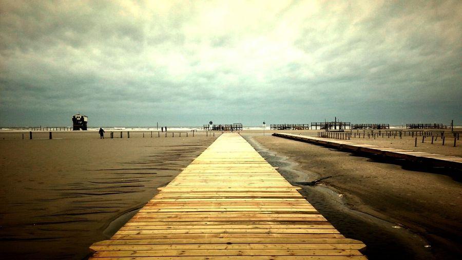 Long wooden jetty on the beach below cloudy sky