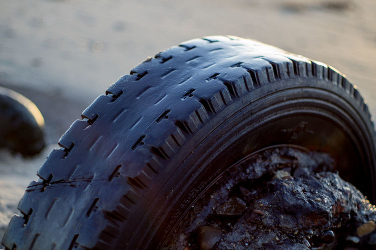 Close-up of tire at beach