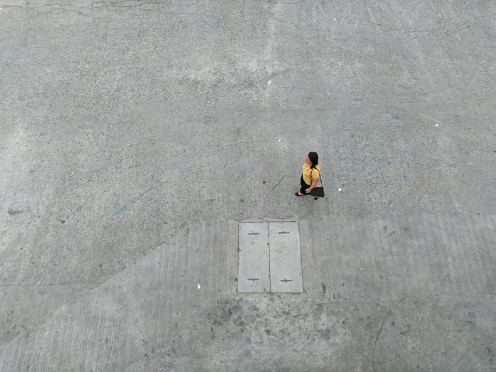 High angle view of woman walking on concrete
