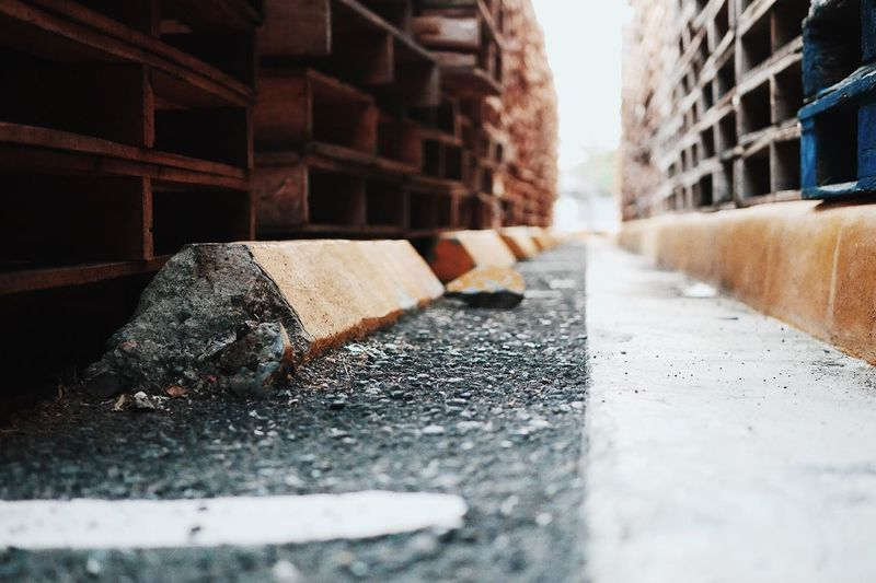Stacked wooden pallets on footpath