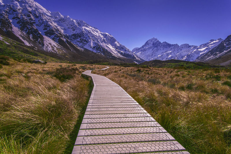 Empty boardwalk against snowcapped mountains