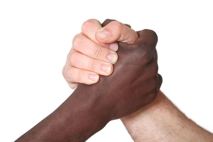 Close-up of arm wrestling over white background