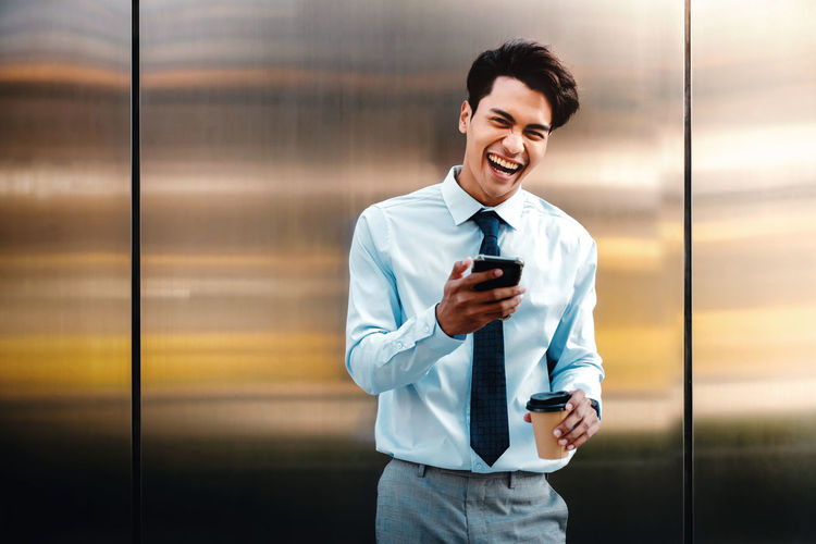 Portrait of smiling young man using mobile phone at office