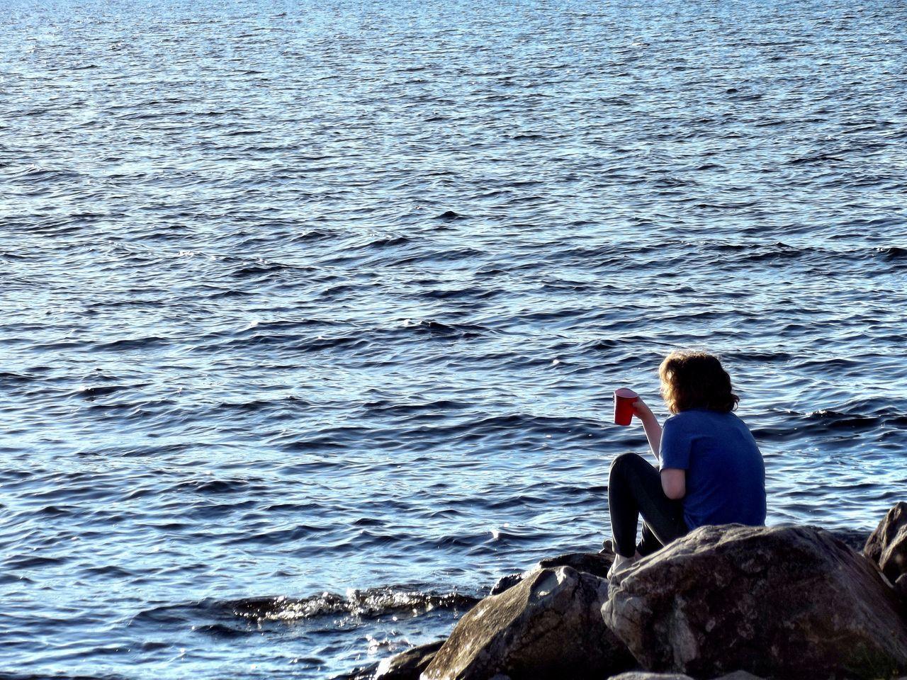 Woman Enjoying Drink At Rock At Seaside