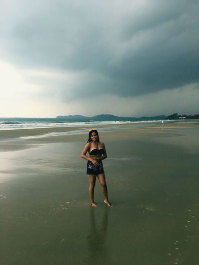 Portrait of woman standing at beach