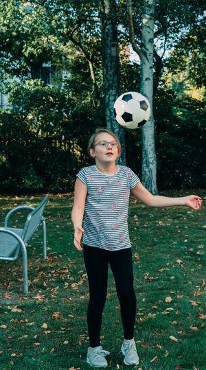 Full length of girl standing on field against trees