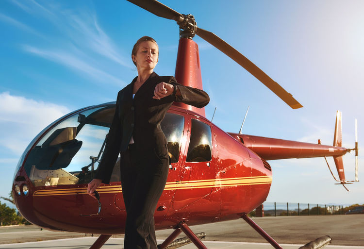 Businesswoman Standing By Helicopter Against Sky