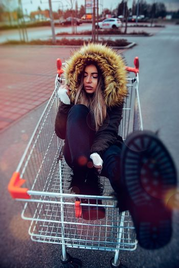 High angle view of young woman sitting in shopping cart on street