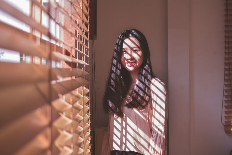 Portrait of smiling young woman with long hair standing by window blinds at home