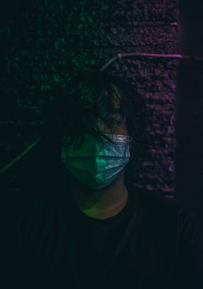 Portrait of man wearing mask in dark
