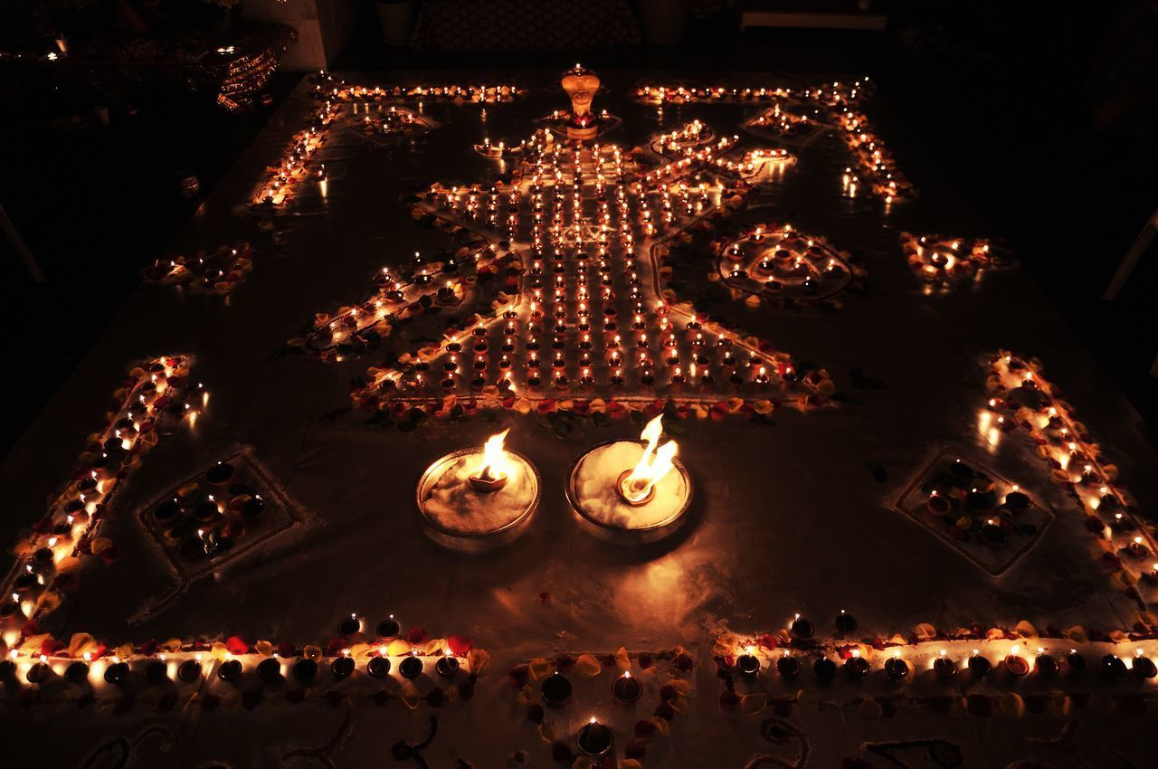 illuminated, flame, burning, glowing, fire, night, indoors, celebration, high angle view, heat - temperature, fire - natural phenomenon, lighting equipment, candle, no people, religion, belief, traditional festival