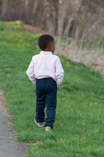 Young Boy Walking Through a Park African American Boy Child Childhood Field Full Length Leisure Activity Lifestyles Nature One Person Outdoors People Real People Rear View Standing Walking