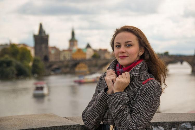 Portrait of woman standing by railing against charles bridge over vltava river