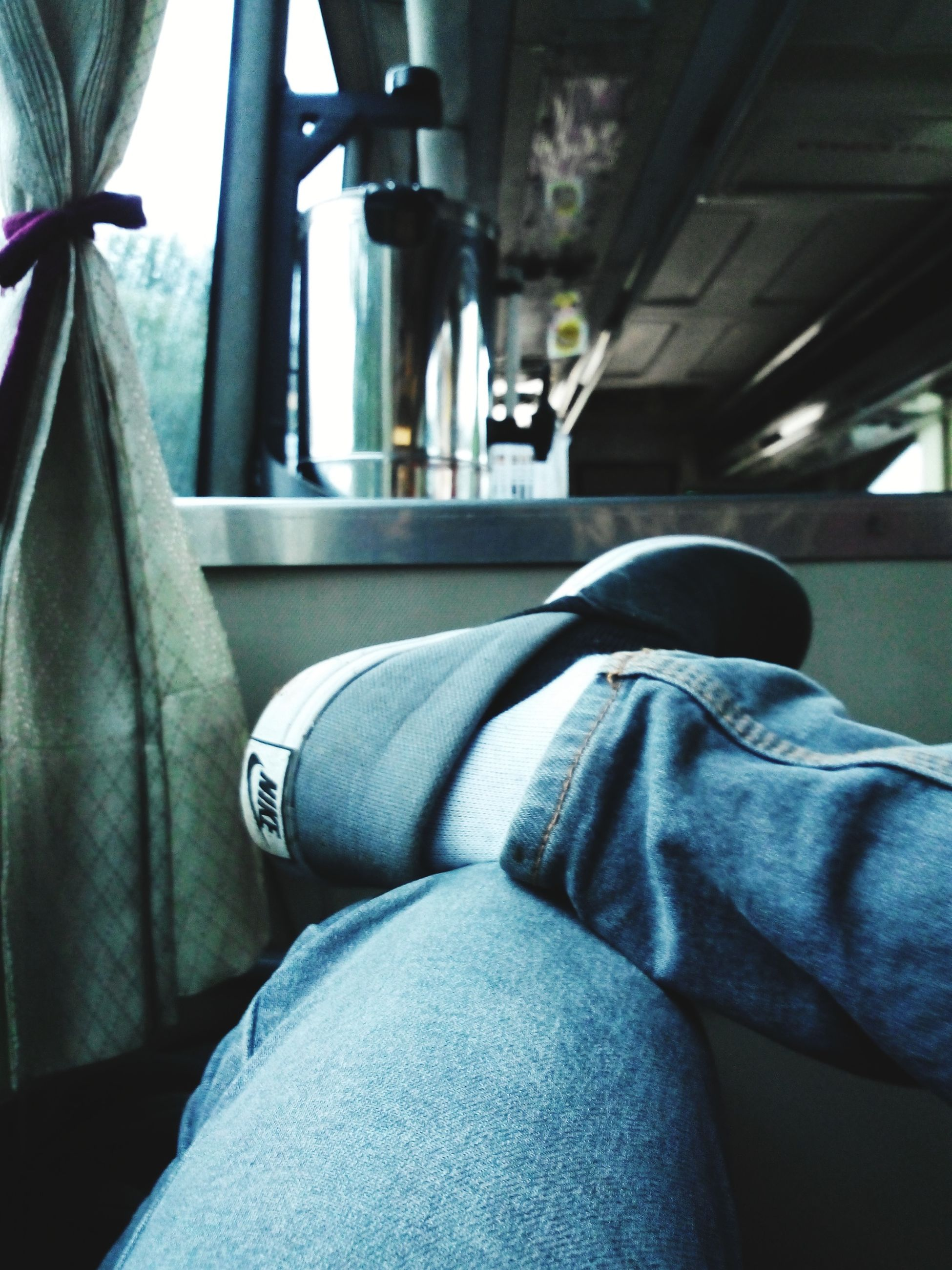 indoors, window, vehicle interior, vehicle seat, transportation, men, sitting, glass - material, lifestyles, jeans, casual clothing, train - vehicle, rear view, mode of transport, transparent, public transportation, low section, home interior