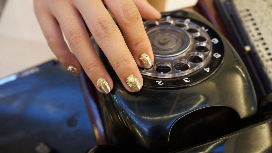 Cropped Hand Of Woman Touching Rotary Phone