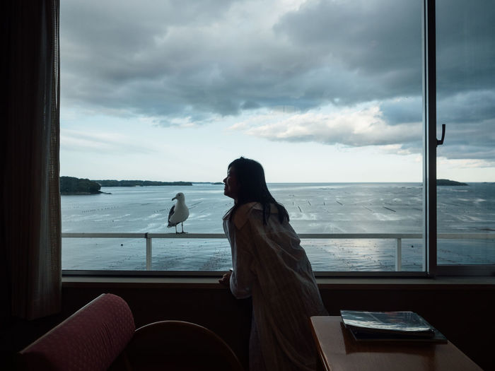 Woman looking at sea seen through window