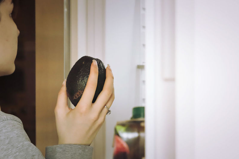 Midsection of woman holding avocado