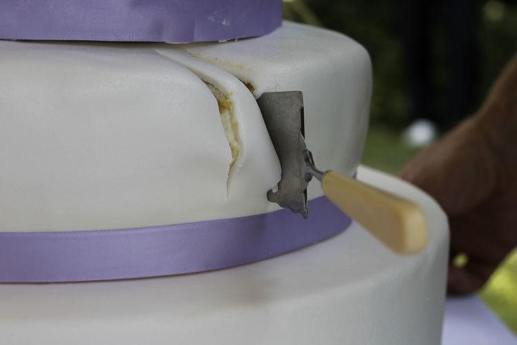 Close-up of wedding cake with server