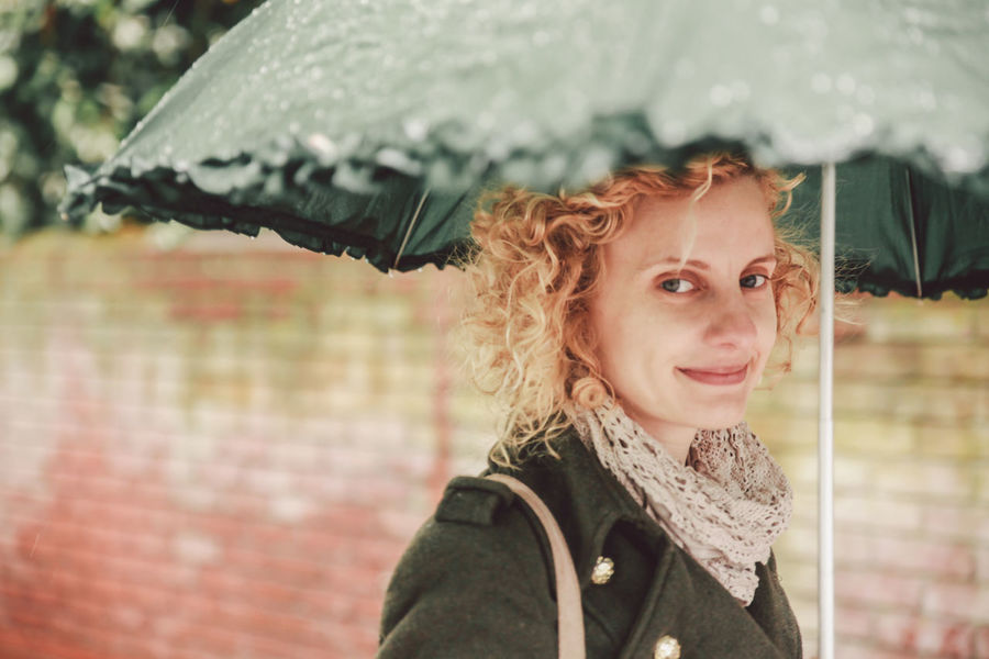 Brick Wall Casual Clothing Confidence  Curly Hair Girl Happiness Long Hair Looking At Camera Portrait Rain Rainy Day Smiling Standing Umbrella Under My Umbrella Under The Umbrella  Waist Up Women Young Women Women Who Inspire You Natural Light Portrait People And Places Exploring Style Connected By Travel Fashion Stories Autumn Mood