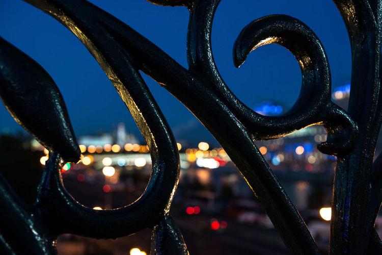 Illuminated City Seen Through Wrought Iron