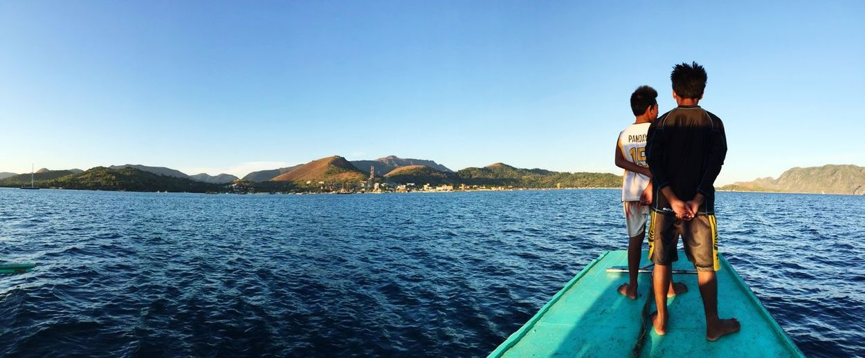 Coron Island Vista #palawan #itsmorefuninthePhilippines EyeEm Selects Two People Water Nautical Vessel Clear Sky Transportation Togetherness Mode Of Transport Day Scenics Men Real People Nature Beauty In Nature Outdoors Lifestyles Sea Love Mountain Blue