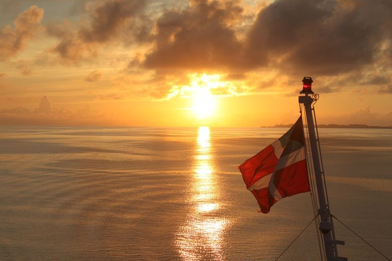 Flag over sea against sky during sunset