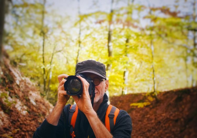 Portrait of man photographing through digital camera in forest