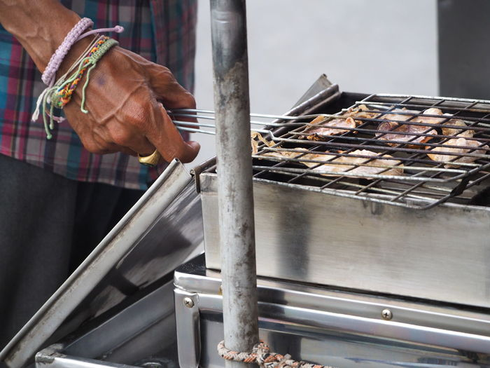 Close-up of human hand preparing seafood on barbecue grill