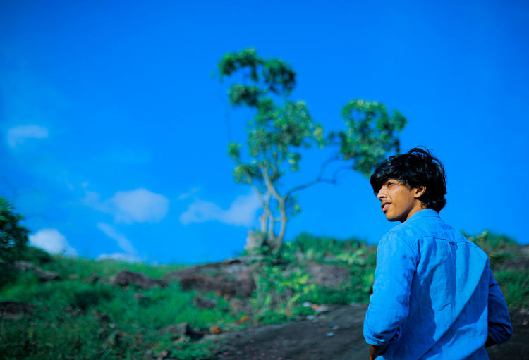 Boy standing against blue sky for a fresh beginning.