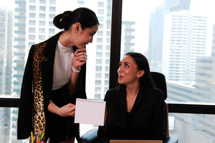 Businesswomen discussing over calendar on table