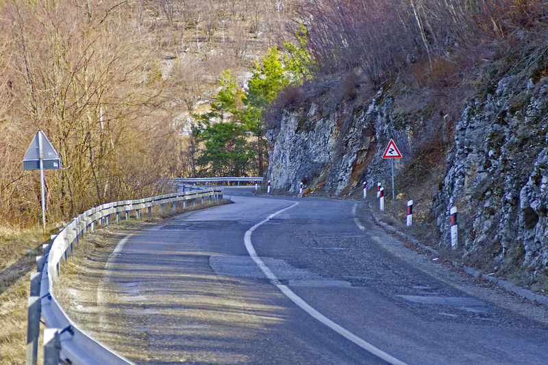 Old mountain road on early spring sunny day Beauty In Nature Day Direction Landscape Mountain Mountain Road Nature No People Outdoors Road Road Marking Rural Scene Scenics - Nature Sign Symbol The Way Forward Transportation Tree