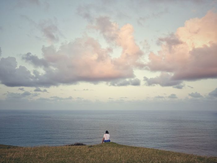 Rear view of woman sitting on mountain by sea against cloudy sky