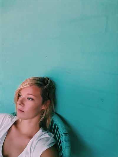 Blonde Calm Relaxing Sitting Blonde Girl Casual Clothing Contemplation Females Headshot Looking One Person Portrait Real People Relaxation Turquoise Colored Wall - Building Feature Women Young Adult Young Women