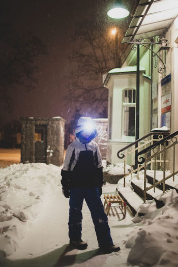 Rear view of man standing on street in city during winter